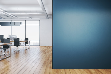 Clean coworking office interior with blank blue wall.