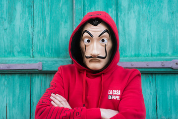 """Mulhouse -  France - May 17 2020 - fan of """"La casa de papel"""" (paper house) in english the serie TV on Netflix, standing with red sweat shirt costume and Salvador Dali mask on green background"""