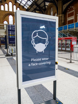 """London, UK. May 16th 2020: Liverpool Street underground train station. A new commuter information board, advice to """"please wear a face covering"""". Face mask to prevent coronavirus, Covid-19 spreading."""