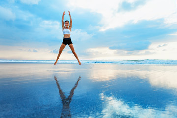 Young woman doing jumping jack or star jumps exercise to burn fat, keep fit. Sunset beach, blue sky...