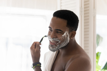 Young african American man look in mirror in bathroom use foam shaving beard with razor, millennial...