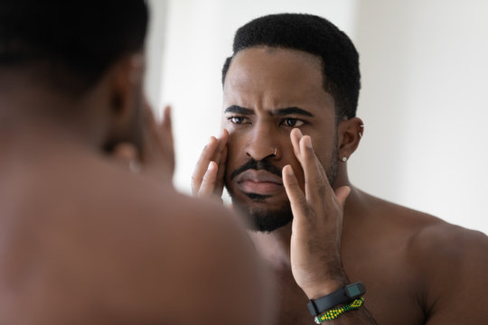 Anxious young african American man look in mirror in bathroom concerned about face wrinkles, frustrated unhappy biracial male worried about acne, unhealthy facial skin, skincare concept