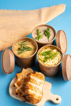 Soup in paper disposable cups for take-out or delivery of food and homemade bread on blue background.