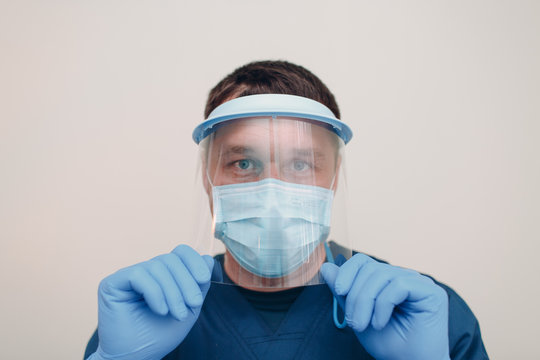 Man in face medical surgical mask with transparent shield mask and gloves.