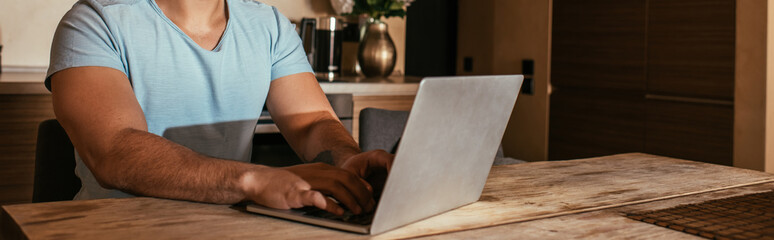 cropped view of male mixed race freelancer working with laptop on kitchen during self isolation, website header