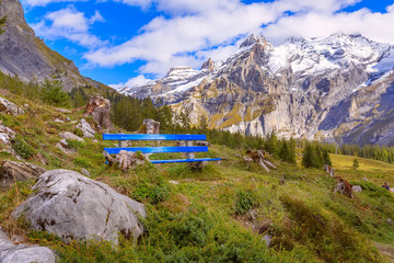 Blue bench on the pathway to Oeschinnensee lake and Swiss Alps panorama, Switzerland