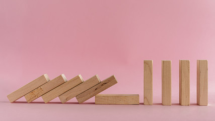 The wooden toys falling down but the next others that is far away could stand for social distancing concept