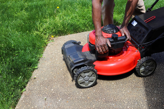 An African-American man fixing a lawnmower
