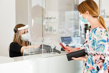 Foto auf Leinwand Texturen dentro un locale commerciale la cliente paga alla cassa con carta di credito munita di mascherina e separata dalla cassiera da un separatore di plexiglass