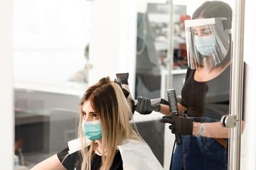 parrucchiera si accinge ad asciugare con un phon i capelli di una di una cliente all'interno di un...