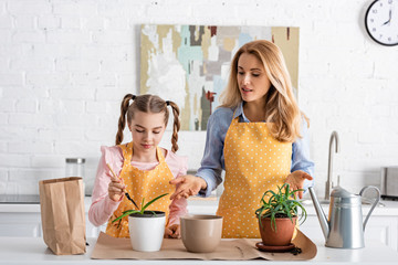 Cute child with mother holding shovel near table with paper bag, flowerpots with aloe and watering...