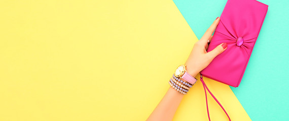 Fashion. Trendy handbag clutch, female hand, accessories set. Minimal design. Stylish wrist watches, jewelry, summer fashionable woman. Creative art shopping concept on yellow, summertime Wall mural