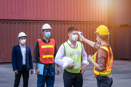 Virus Covid 19 crisis Staff check fever by digital thermometer visitor before entering the work for scan and protect from Coronavirus or COVID-19, Engineer and factory concept at container yard
