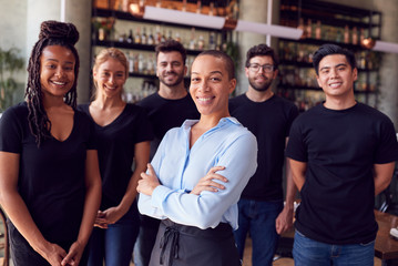 Portrait Of Female Owner Of Restaurant Bar With Team Of Waiting Staff Standing By Counter