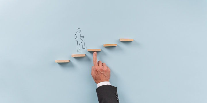 Hand of a businessman supporting wooden step for a silhouetted man to walk upwards