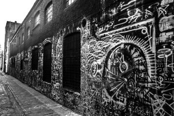 Graffiti's street. Black and white picture of a narrow street where the walls are all tagged with graffitis.