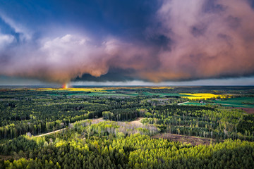 Fotobehang Lavendel Aerial landscape of countryside with colorful storm clouds. Extreme thunderstorm over a pine forest and road.