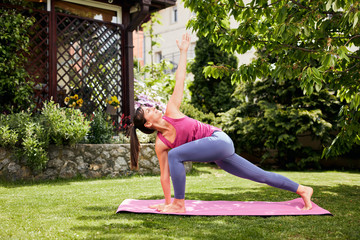 Young attractive brunette standing on the mat in her backyard in practicing yoga. Revolved Crescent Lunge with Arms Extended yoga pose.