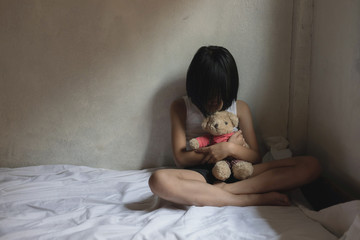 Lonely scared little girl sitting in bed room, hugging her teddy bear and crying. Child abuse