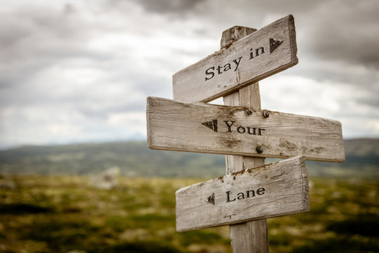stay in your lane text engraved on wooden signpost outdoors in nature.