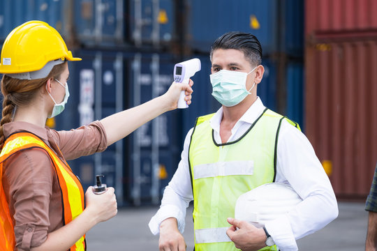 American engineers wear mask to prevent coronavirus (Covid-19) and used thermoscan to check the temperature of worker. Standing at the container shipping area. Industrial and COVID protection concept.