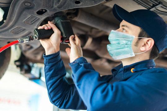Mechanician changing car wheel in auto repair shop wearing a mask, coronavirus concept