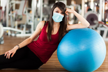Beautiful athletic womanposing against a blue ball wearing a mask, coronavirus concept