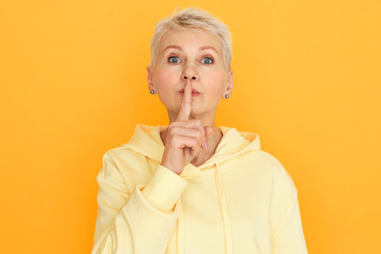 Portrait of blue eyed blonde mature woman in hoodie holding fore finger on her lips, shushing, asking to keep silent and be quiet. Emotional retired female saying Shh. Conspiracy theory concept