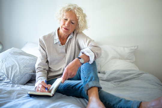 older woman sitting on bed writing in diary