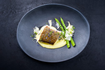 Traditional fried skrei cod fish filet with green asparagus tips and mashed potato creme in...