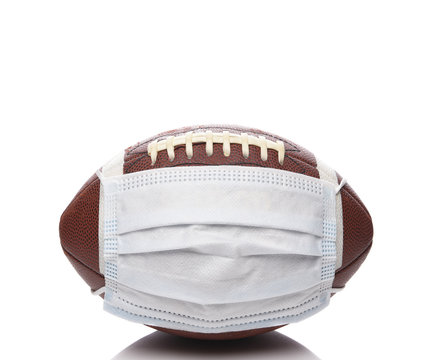 Sports and Covid-19 Concept.  An american Foortball with a surgical mask.
