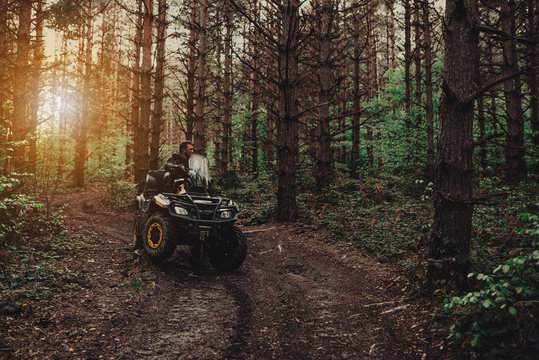 A young man in a white helmet rides through the woods on a Quad bike. Extreme hobby. A trip to ATV on the road from logs. Quad Biking through the forest.