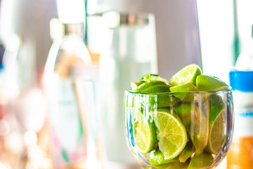 A glass full of freshly cut limes standing on a bar counter ready to be made into a cocktail drink at a party