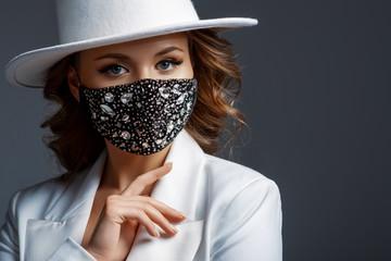 Elegant woman wearing trendy fashion outfit during quarantine of coronavirus outbreak. White suit...