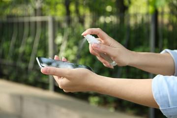 Woman spraying antiseptic onto smartphone outdoors, closeup