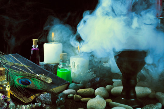 Magic potions, crystals, book, stones, peacock feather, and candles with smoke on a black background.