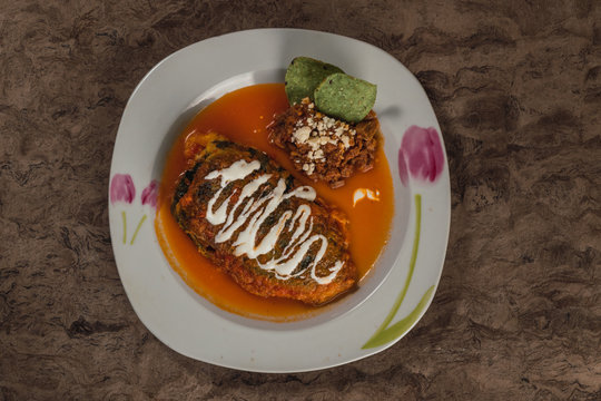 Chiles Rellenos, typical Mexican dish, poblano chiles stuffed with ground meat, Oaxaca cheese, covered with egg, accompanied by tomato caldillo and cream beans with tortilla chips. Aerial photo.