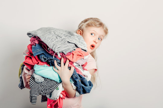 Mommy little helper. Cute Caucasian girl sorting clothes. Adorable funny child arranging organazing clothing. Kid holding messy stack pile of clothes, things. Home chores housework.
