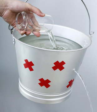 Hand pouring water from a glass into a leaking pail