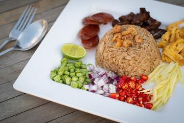 Obraz Thai food - Kao Cluk Ka Pi (Mixed Cooked Rice with Shrimp Paste Sauce) on white round dish. Fried rice with Shrimp paste, Thai style food. Thailand's national dishes. - fototapety do salonu