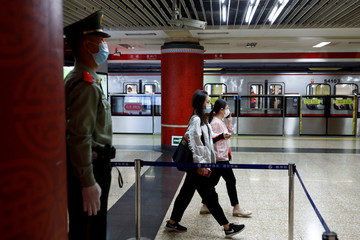 A Paramilitary police officers keeps watch at a station of Line 1 of the metro that runs past the Great Hall of the People