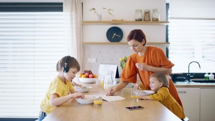 Wall Mural - Mother with small children in kitchen in the morning at home, eating breakfast.