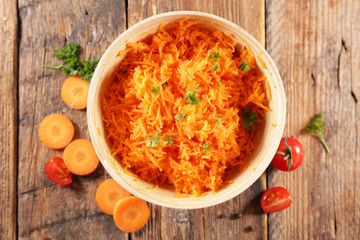 Wall Mural - fresh grated carrot on wood background