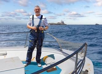 The captain of a ship stands at the bow with binoculars and looks into the camera. In the background the small Spanish rocky island Isla Hormiga, which translates as an ant island.