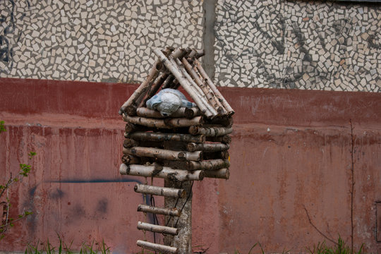 Decor of the garden in the courtyard of an apartment building in a provincial city - a hut on one leg of sticks, from which peeps a toy bear