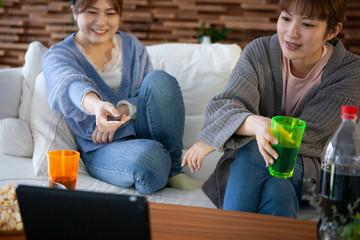 家のソファーでテレビを楽しむ女性たち