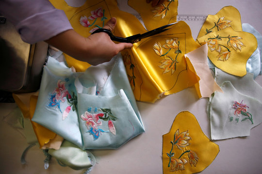 Worker cuts patterns off a silk cloth for making face masks designed by Zhou Li, at a studio in Beijing