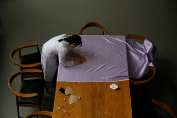 Worker wearing a face mask draw patterns on a piece of silk cloth for making face masks designed by Zhou Li, at a studio in Beijing