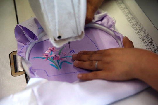 Worker uses a sewing machine to embroider Chinese characters on a silk cloth for making a face mask designed by Zhou Li, at a studio in Beijing