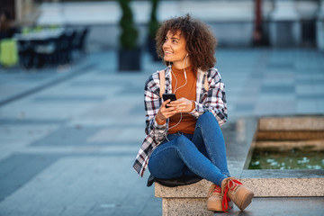 Young attractive mixed race woman sitting on fountain, using smart phone and enjoying music.